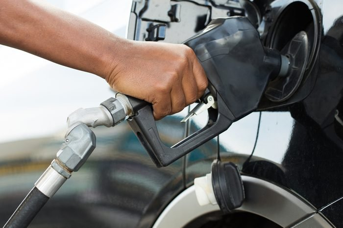 A man's hand filling up a car with gas or petrol at a gas station.