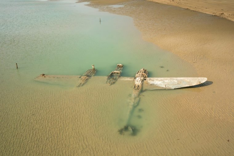 The wrech of a crashed WW2 P38 Lightning Aircraft laying on a beach in Wales, UK