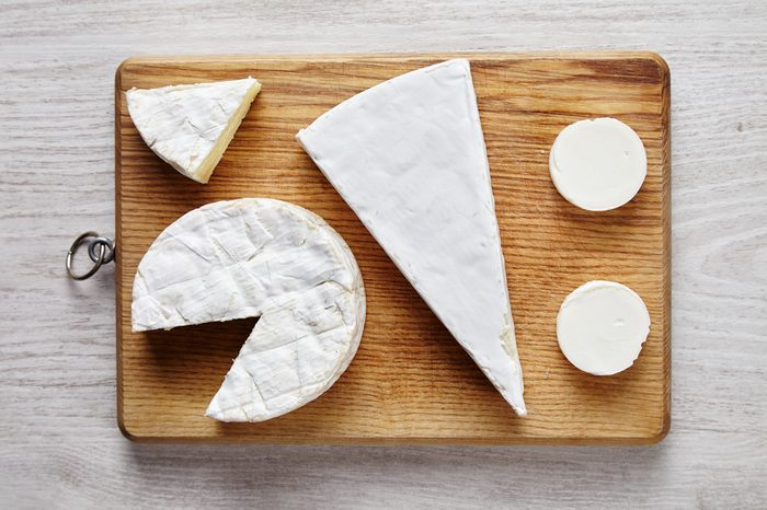 Avangard white soft cheeses: goat, brie, camembert on wooden des