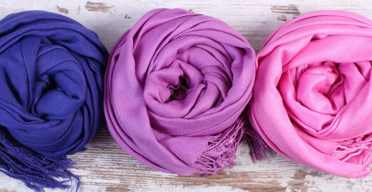 Colorful scarves on old rustic wooden background, womanly accessories, warm clothing for autumn or winter