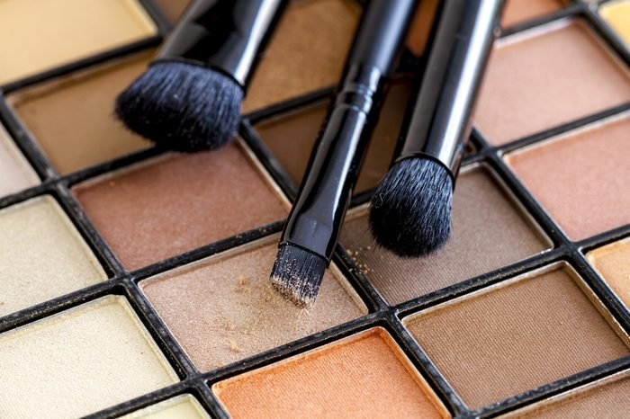 Three cosmetic brushes with light brown eye shadow dust sitting on top of palette of pale nude eye shadow shades