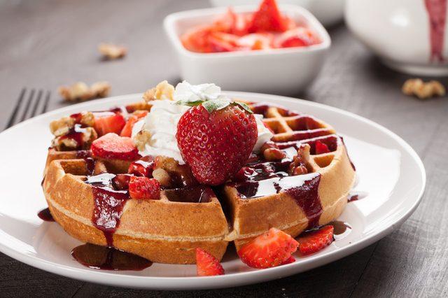 Whole wheat Belgium waffle topped with boysenberry syrup, whipped cream, walnuts, and freshly chopped strawberries horizontal shot