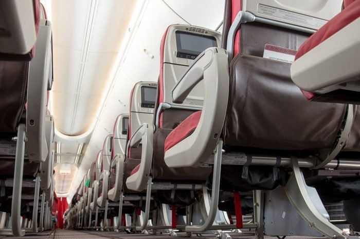 Aisle seats on planes from below view. An empty row of seats in a airplane. Rear side chairs with monitors on the aircraft.
