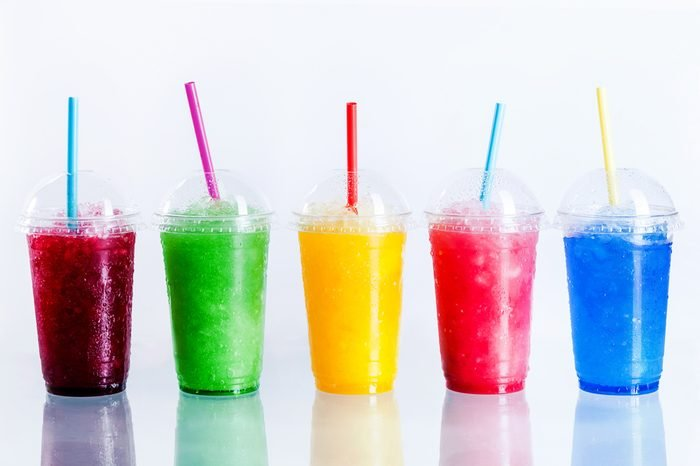 Panoramic Still Life of Colorful Frozen Fruit Slush Granita Drinks in Plastic Take-Away Cups with Lids and Drinking Straws in front of White Background