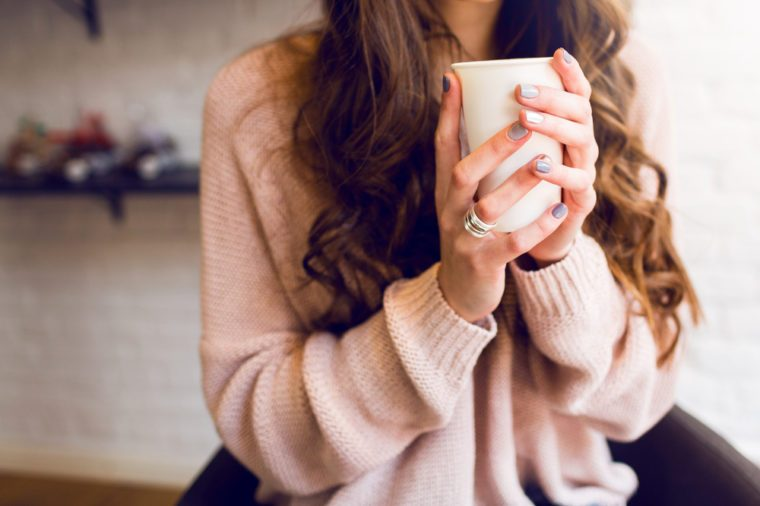 Pretty young woman in stylish pink sweater holding coffee or cappuccino in hands. Warm soft cozy image. Details.