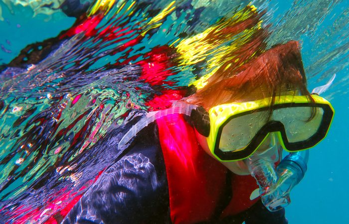 Little girl (age 5-6) snorkeling dive in the Great Barrier Reef Queensland Australia