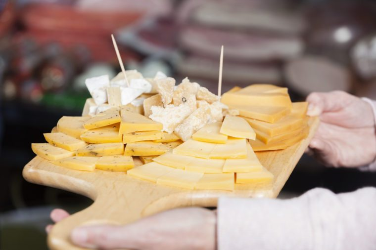 Saleswoman Holding Cutting Board With Various Cheese