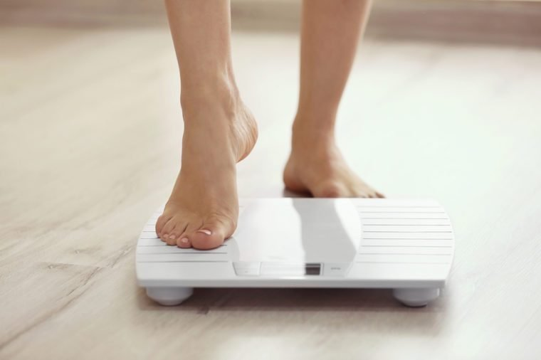 Female leg stepping on floor scales
