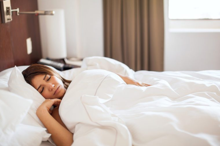 Beautiful young brunette getting some rest and sleeping late in the morning in a hotel bed