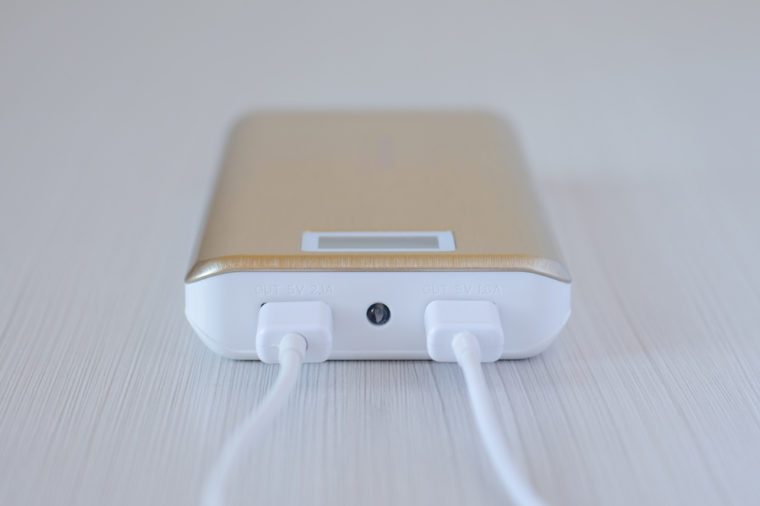 Golden power bank for mobile phone with a usb cable. Close-up
