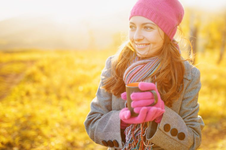 Young smiling woman with coffee mug in hands enjoying the fall season. Woman wearing fashionable colorful striped scarf, purplish-red hat and gloves on nature background. Outdoor portrait in autumn.