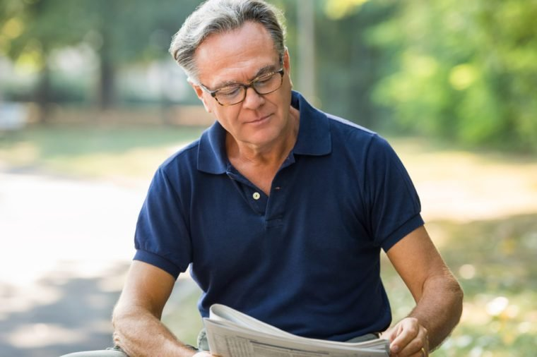 Senior man sitting at park and reading newspaper. Mature man wearing glasses while reading the finance section in a newspaper. Retired pensioner sitting in the park holding a newspaper.