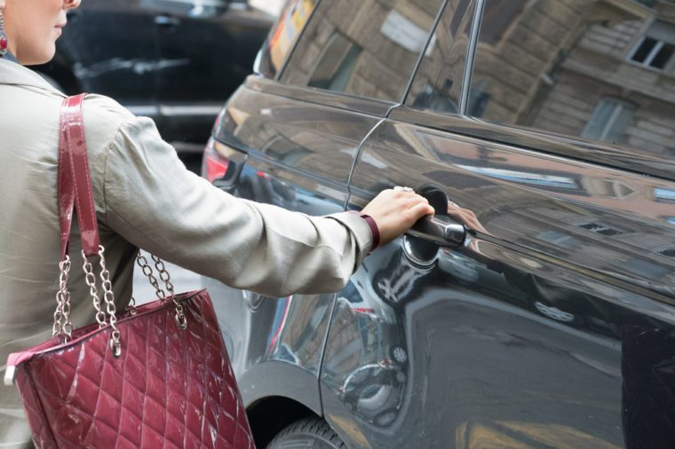 Woman with a bag is entering in a luxury car
