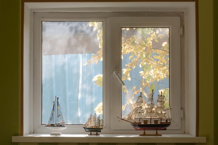 a window in the bedroom, a collection of ship models, a view of the street with trees