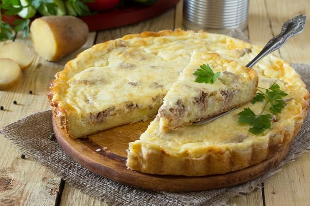 A classic quiche Lorraine pie with potatoes, meat and cheese on a wooden table. Space for your text.
