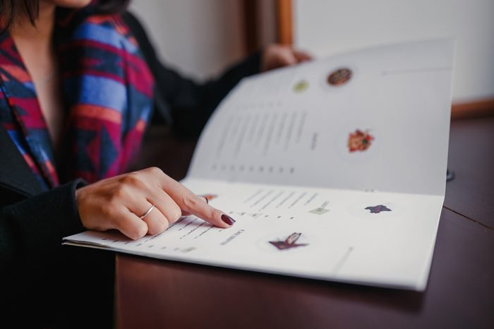 close up of woman finger with menu choosing dishes at restaurant
