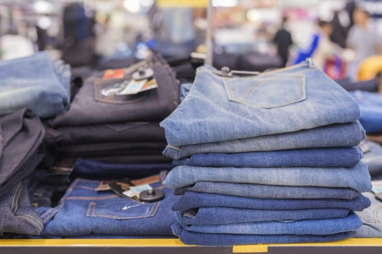 Advertise concept. Lot of different blue jeans Blue jeans on tables in clothes store on background blur supermarket. (lens blur effect)