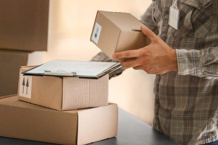 Courier holding carton box, closeup