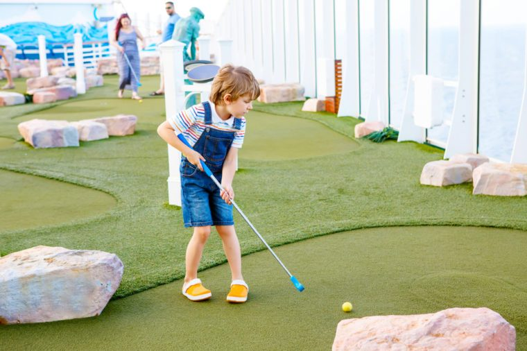 Little kid boy playing mini golf on a cruise liner. Child having fun with active leisure on vacations.