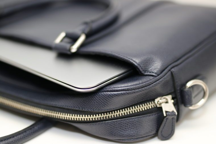Closeup of blue leather briefcase business work bag with laptop inside