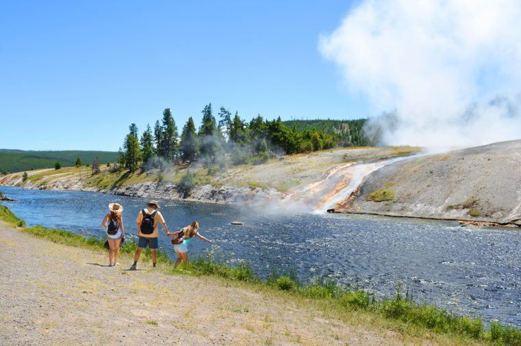 Family hiking on summer vacation. Father holding child's hand. The water from the springs flowing into the Firehole River, Yellowstone National Park. Wyoming, USA.