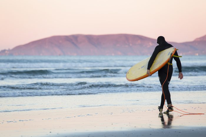 Surfer with surfboard and wetsuit walks towards the water at sunrise in Pismo Beach
