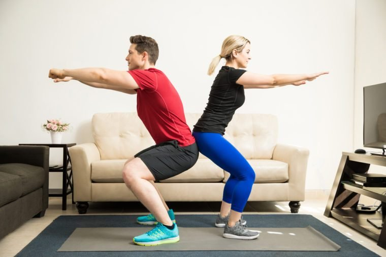 Profile view of a young Latin couple exercising and doing some squats together at home