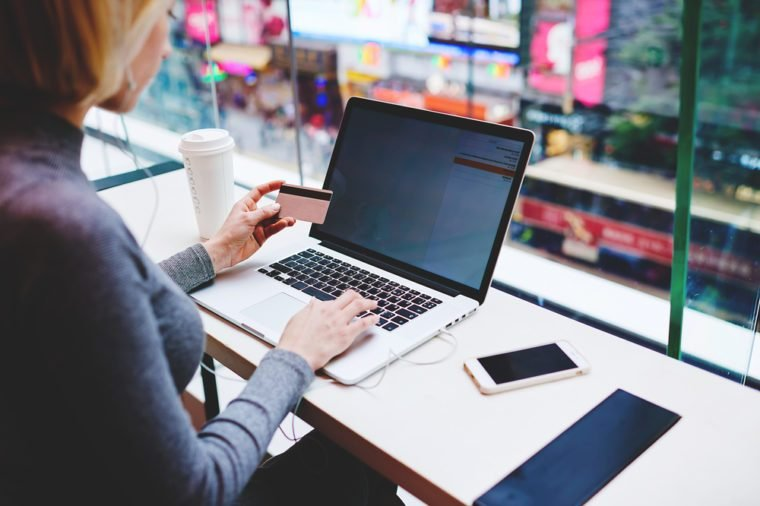 Woman using laptop computer for order online ticket on airplane for travel. Female paying with plastic credit card her shopping in internet while sitting in coffee shop. Payment with data protection