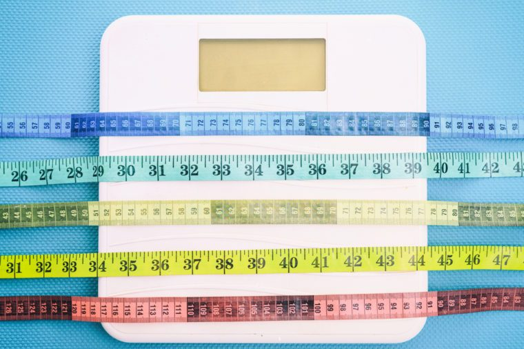Bathroom scale and measure tapes on a blue background