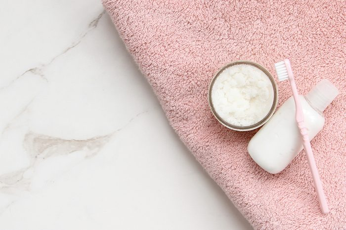 Top view of styled pink bath towel with white and pink bath products against open white marble table top.