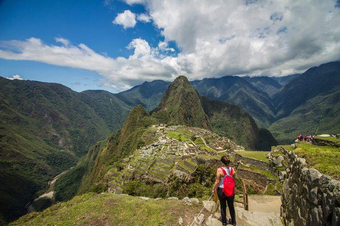 Young Adventure Girl traveler observinng in front of the Majestic Machu Picchu ruins- Peru.