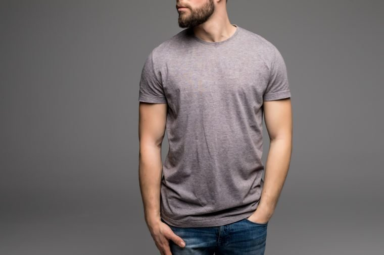 A man in a grey t-shirt and denims holds his hands in pockets. Isolated on grey