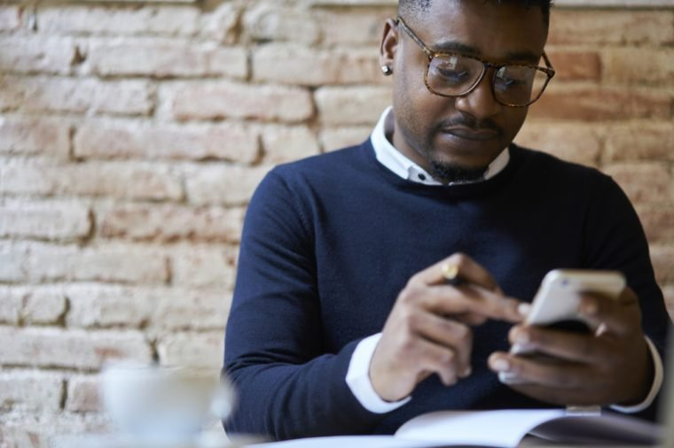 Cropped image of afro american international student in spectacles browsing internet websites on smartphone in searching useful languages seminars for studying remote using free wifi in coffee shop