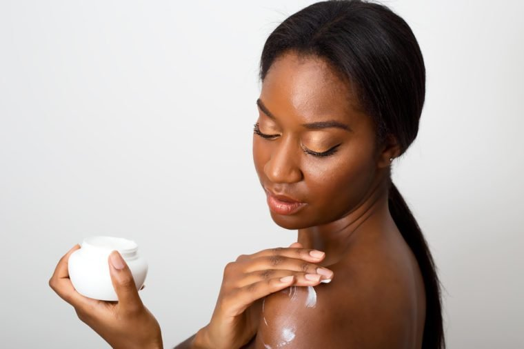 african american beauty applying skin cream