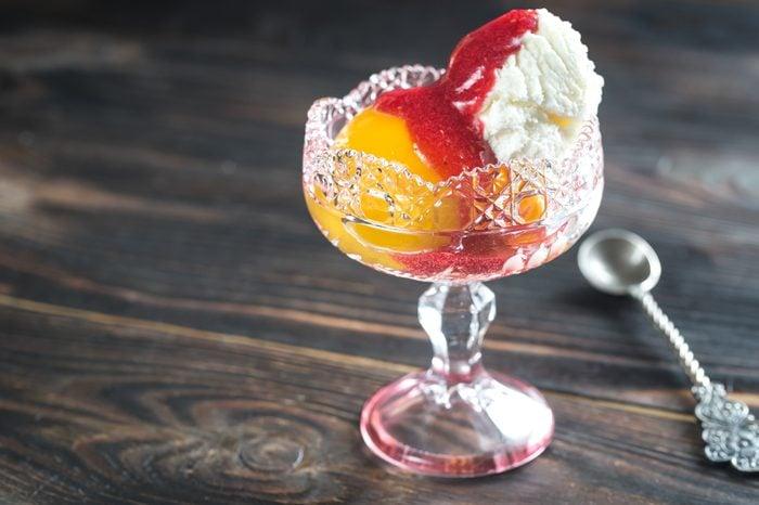 Bowl of Peach Melba - vanilla ice cream with peaches and raspberry sauce