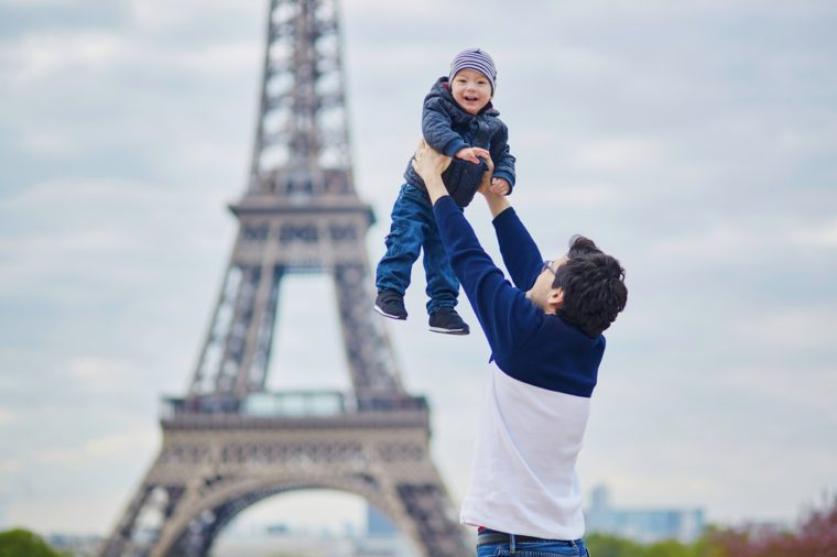 Father throwing his little son in the air near the Eiffel tower in Paris. Happy family of two enjoying their vacation in France.