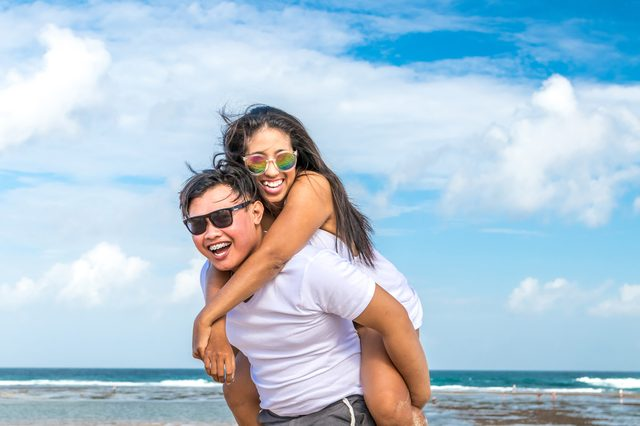 Asian couple having fun on the beach of tropical Bali island, Indonesia.