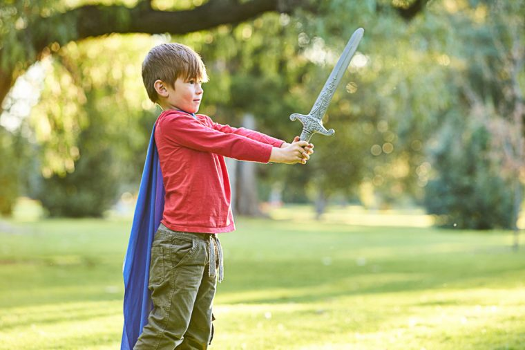 boy playing with toy sword in park