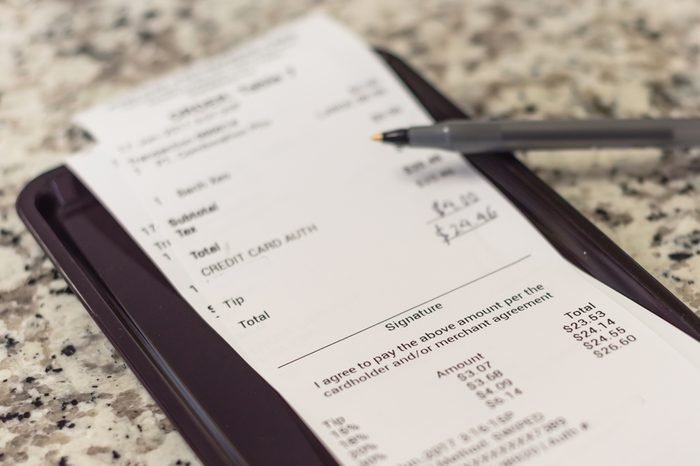 Soft focus, shallow DOF a receipt with hand written total amount and tipping from Vietnamese restaurant. Paper invoice with suggested gratuities/tips on plastic tray, open pen on top of marble table.