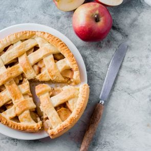Popular American apple pie piece and cup of tea on gray table background. Homemade classical friut tart. Copy space,top view