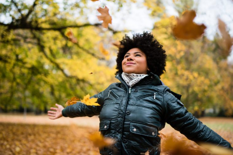 Smiling carefree woman in autumn park, arms outstretched.