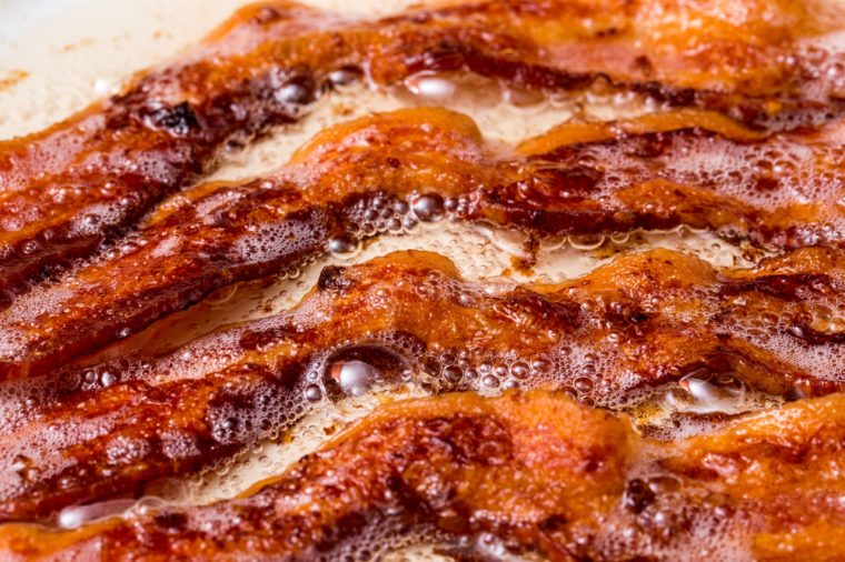 bacon cooked cooking in white pan skillet on flat top stove