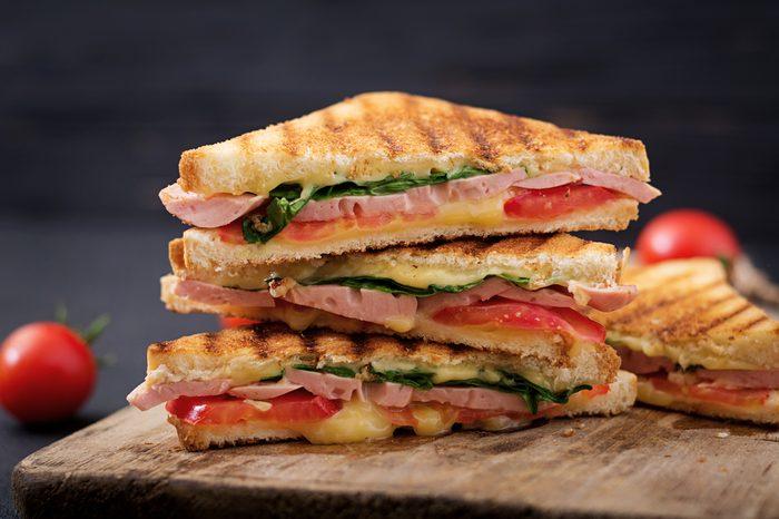 Club sandwich panini with ham, tomato, cheese and basil