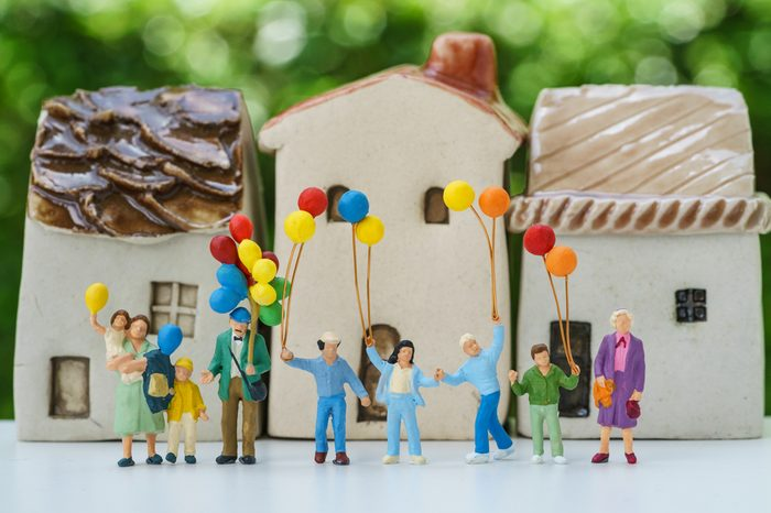 Miniature people with happy family holding balloons with ceramic house as property or mortgage concept.