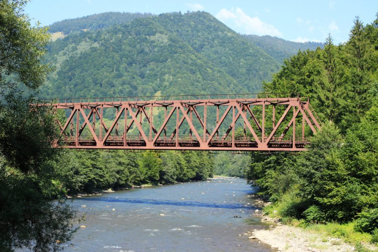 A metal bridge across a mountain river.