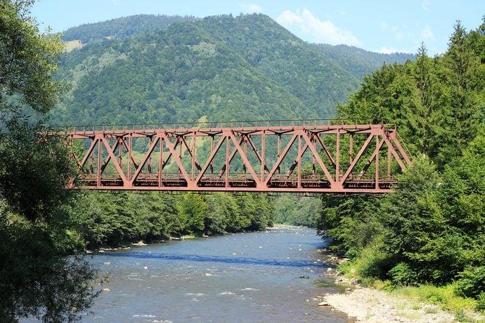 A metal bridge across a mountain river.