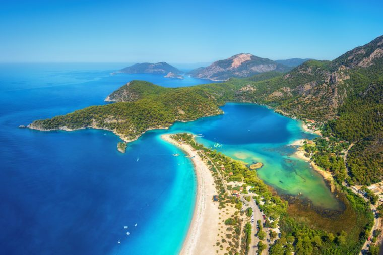 Amazing aerial view of Blue Lagoon in Oludeniz, Turkey. Summer landscape with mountains, green forest, azure water, sandy beach and blue sky in bright sunny day. Travel background. Top view. Nature