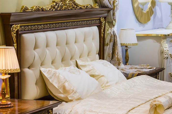 Luxury white bedroom in antique style with rich decor and bedside lamps