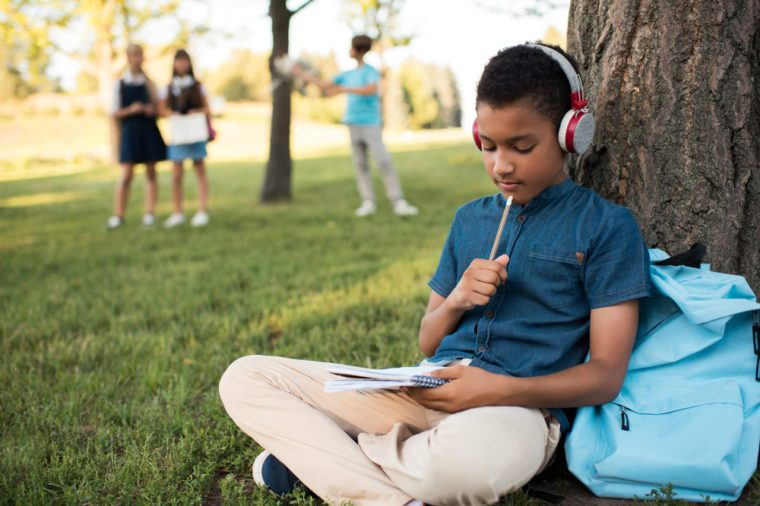 pensive african american boy in headphones taking notes and studying in park