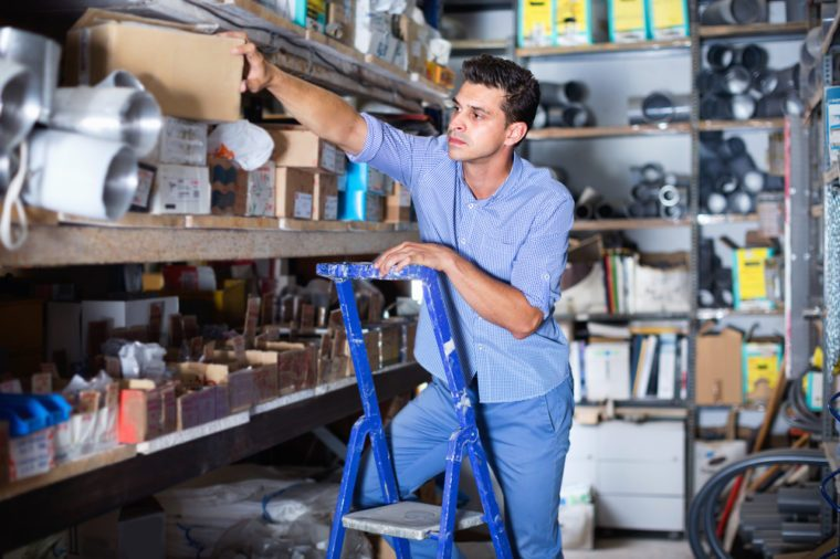 Smiling man in unifom is using ladder to reach the top shelves in the building store.